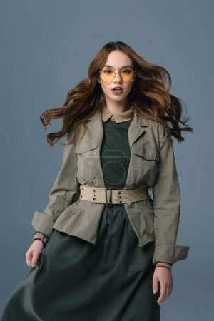 beautiful stylish girl posing in autumn outfit for fashion shoot, isolated on grey