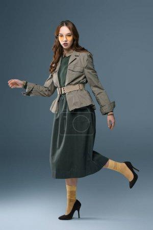 Photo pour Femme élégante qui pose en tenue d'automne pour Shooting de mode, isolé sur fond gris - image libre de droit