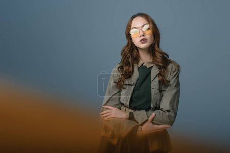 beautiful stylish girl posing in autumn outfit and yellow sunglasses, isolated on grey