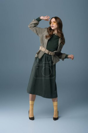 attractive stylish girl posing in trendy autumn outfit, isolated on grey