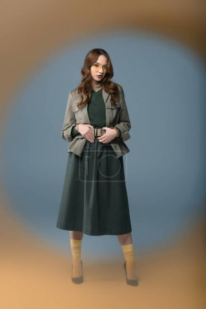 fashionable model posing in autumn outfit, isolated on grey with orange filter
