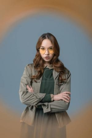 beautiful stylish girl posing with crossed arms, isolated on grey with orange filter