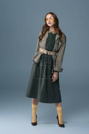 Foto de Hermosa chica con estilo, posando en traje de otoño para sesión de moda, aislado en gris - Imagen libre de derechos