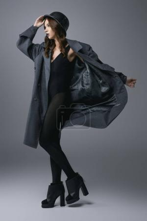 fashionable girl posing in bodysuit, autumn coat and military helmet, isolated on grey