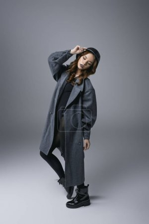 attractive sensual girl posing in autumn coat and military helmet, isolated on grey