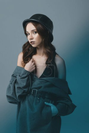 attractive girl posing in autumn coat and military helmet, isolated on grey with blue filter
