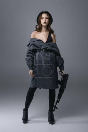 seductive beautiful woman posing in coat and military helmet with rifle, isolated on grey