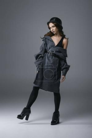seductive fashionable girl posing in autumn coat and military helmet, isolated on grey