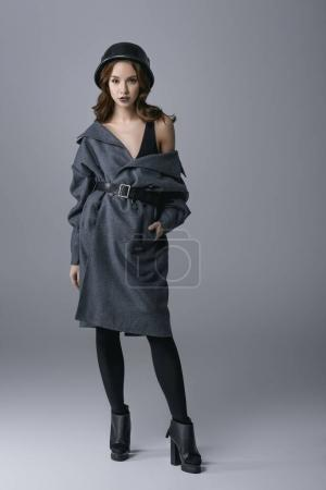 fashionable girl posing in autumn coat and military helmet, isolated on grey