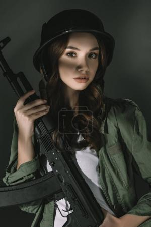 Photo for Beautiful caucasian young girl in military helmet with rifle, on grey with shadows - Royalty Free Image