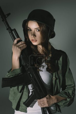 attractive young girl in military helmet with rifle, on grey with shadows