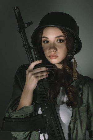 Photo pour Belle jeune femme au casque militaire avec fusil, sur gris avec ombres - image libre de droit