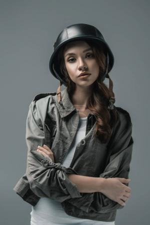 Photo for Beautiful girl posing in military helmet with crossed arms, isolated on grey - Royalty Free Image