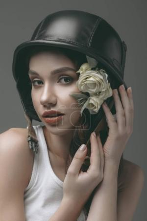 tender girl in military helmet with flowers, isolated on grey