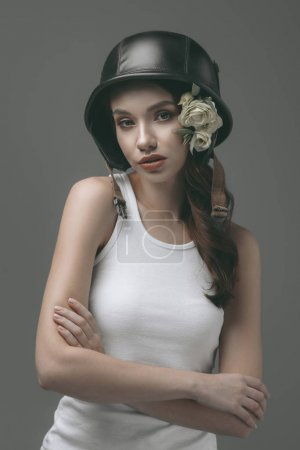 attractive girl in military helmet with white flowers, isolated on grey