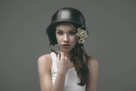 tender young woman in military helmet with flowers, isolated on grey
