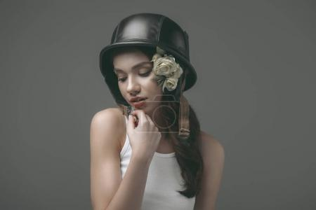 beautiful tender young girl in military helmet with flowers, isolated on grey