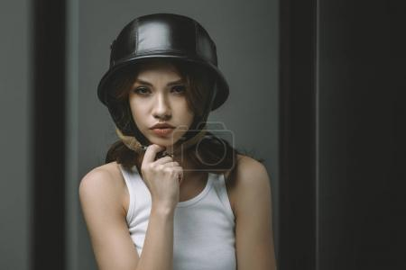 thoughtful young girl in military helmet for fashion shoot