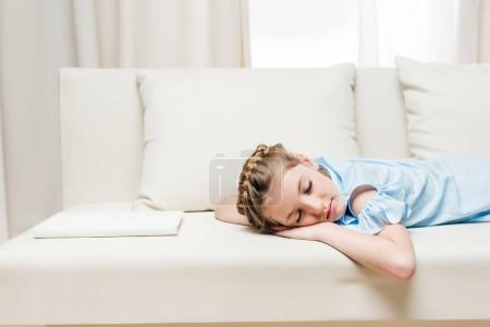 girl sleeping on sofa with book