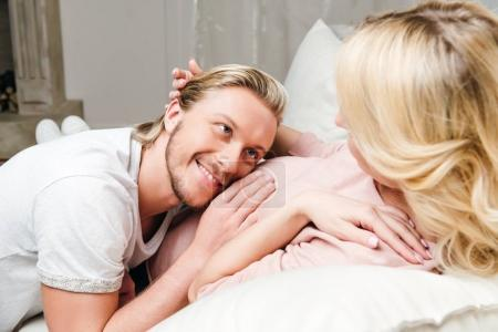 Photo for Happy man hugging pregnant wife and listening belly at home - Royalty Free Image