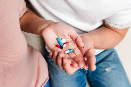 Photo pour Plan recadré de jeune couple tenant diverses pilules sur les paumes - image libre de droit