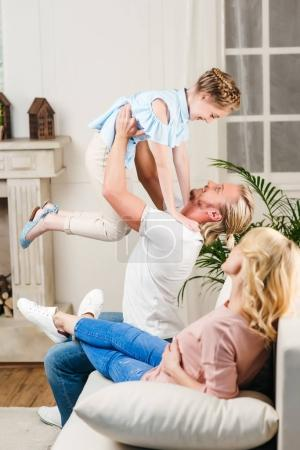 Photo for Side view of father playing together with little smiling daughter with pregnant woman near by at home - Royalty Free Image