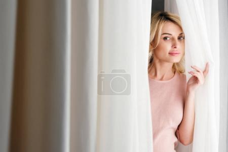 woman looking out of curtain