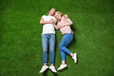 pregnant woman with boyfriend lying on grass
