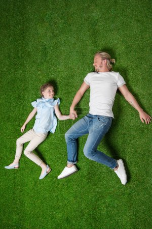 Father with daughter lying on grass