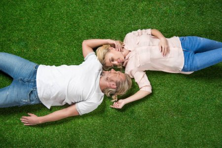 sweethearts lying on grass