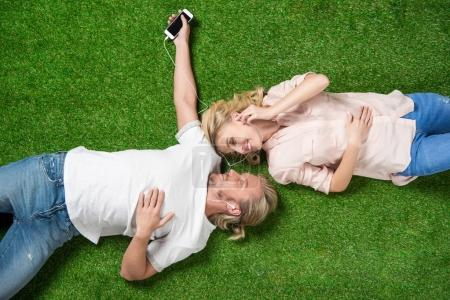 sweethearts listening music on grass