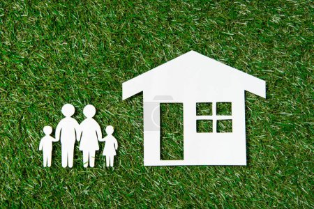 Photo for Top view of paper figures of family and house on grass - Royalty Free Image