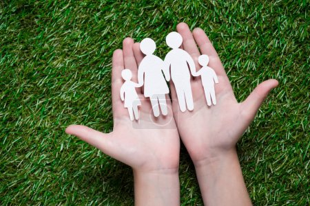 Photo for Human hands holding paper cut of family on grass - Royalty Free Image