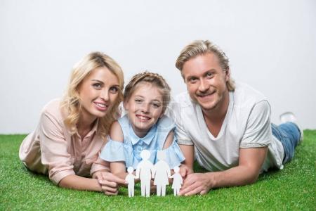 Photo pour Portrait de famille heureuse couché sur l'herbe et la tenue de papier coupé de famille - image libre de droit