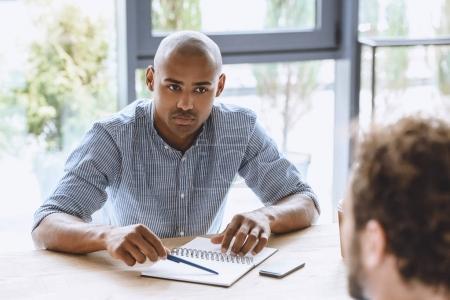 Photo pour Portrait d'un homme d'affaires afro-américain concentré à l'écoute d'un collègue lors d'une réunion d'affaires - image libre de droit
