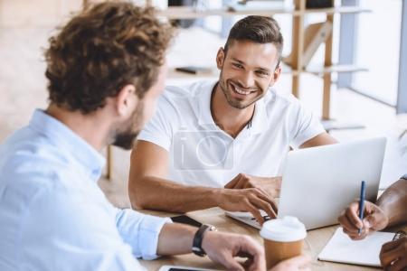 Photo pour Portrait d'homme d'affaires souriant avec ordinateur portable sur la réunion avec ses collègues au bureau - image libre de droit