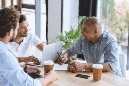 Photo for Multicultural businessmen working on laptop and discussing business strategy in office - Royalty Free Image