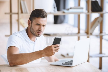 businessman with smartphone at workplace