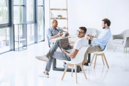 Photo for Multicultural group of businessmen sitting at workplace in light modern office - Royalty Free Image