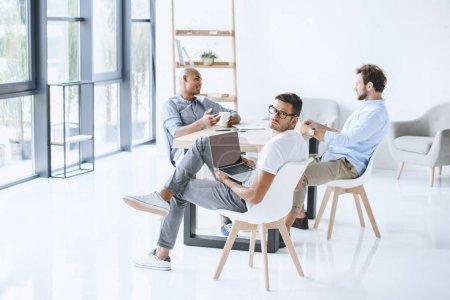 Photo pour Groupe multiculturel d'hommes d'affaires, assis au milieu de travail léger de bureau modern - image libre de droit