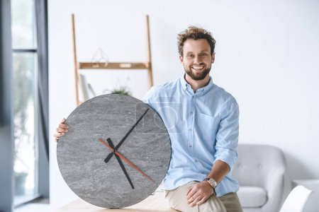 Smiling businessman with clock