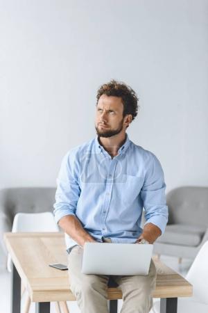Photo pour Homme d'affaires réfléchi assis sur la table avec ordinateur portable sur les genoux au bureau - image libre de droit
