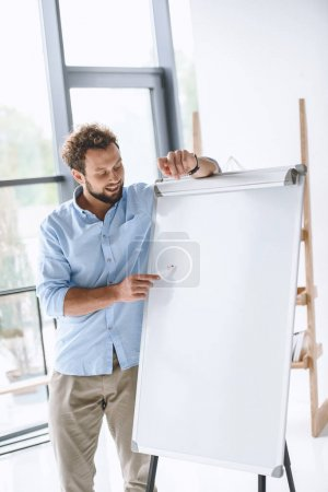 Photo for Young businessman making presentation at white board in office - Royalty Free Image