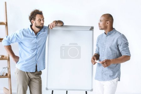 Photo for Multiethnic businessmen standing near white board during business presentation - Royalty Free Image