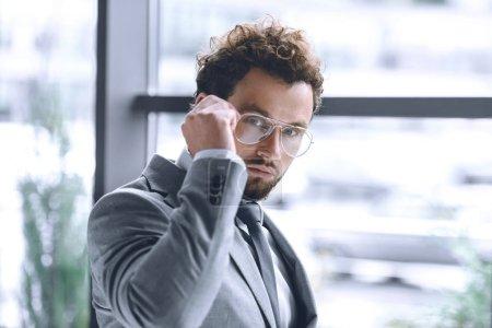 Photo pour Portrait d'homme d'affaires élégant confiant dans des lunettes et costume regardant la caméra - image libre de droit