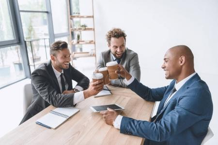 Photo for Multicultural group of smiling businessmen clinking disposable cups of coffee at meeting - Royalty Free Image