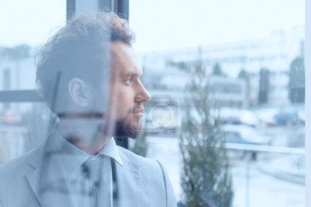 Photo for Portrait of thoughtful businessman in suit looking out window in office - Royalty Free Image