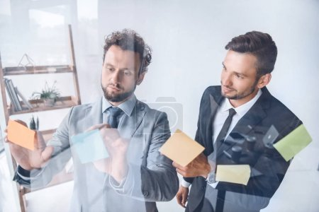 Photo pour Jeunes hommes d'affaires, mettant les notes collantes sur verre alors qu'il travaillait au bureau - image libre de droit