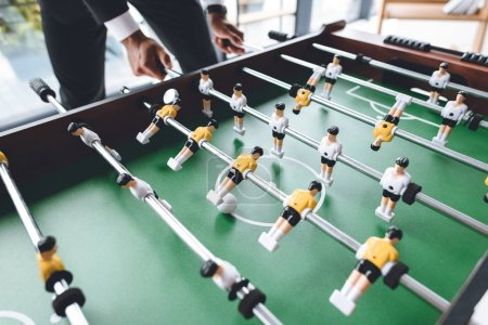 Photo for Close up view of businessman playing table football during break - Royalty Free Image