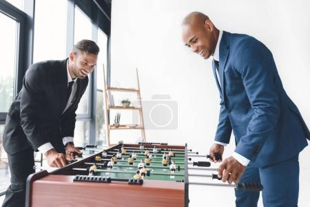 Photo for Side view of happy businessmen playing table football together - Royalty Free Image